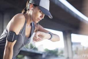 Woman looking at watch after exercising on city street