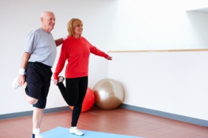 Senior man holds onto his wife for support as they both balance on one leg at the gym.