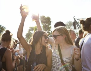 Girlfriends cheering with beer at concert outside